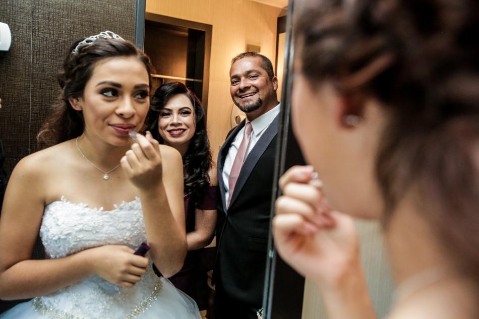 Joven quinceañera observando a sus padres mientras se prepara para su noche única