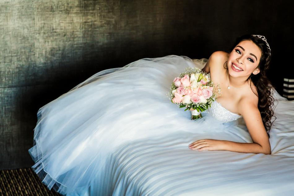 Quinceañera recostada en cama del hotel